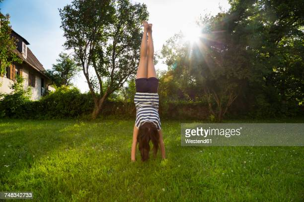 Back view of girl doing handstand on a meadow