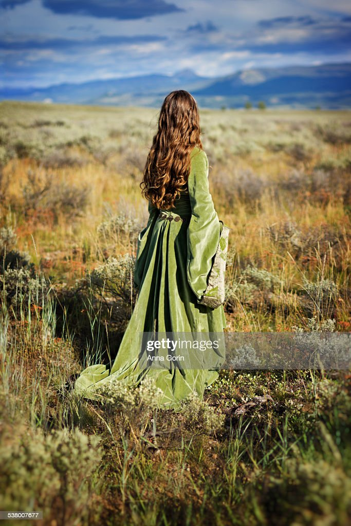 Back view of girl in medieval dress in sage field : Stock Photo