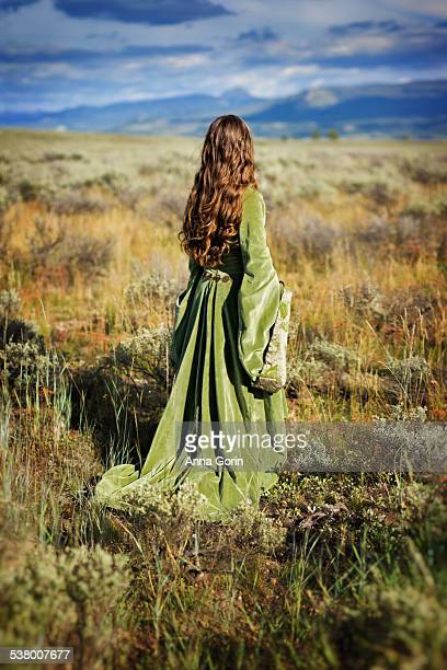 Back view of girl in medieval dress in sage field