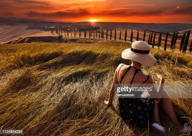 back view of girl in yellow field at sunset tuscany, italy - val d'orcia foto e immagini stock