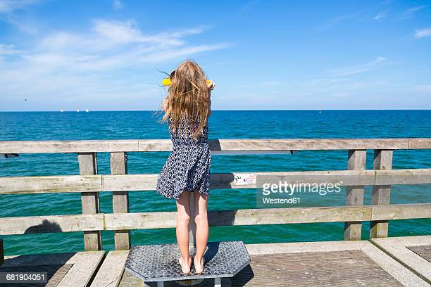 Back view of girl looking to the sea through telescope