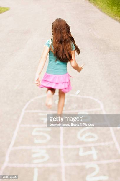 Back view of girl playing hopscotch