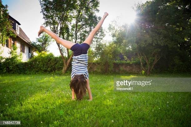 back view of girl turning cartwheel on a meadow - hausgarten stock-fotos und bilder