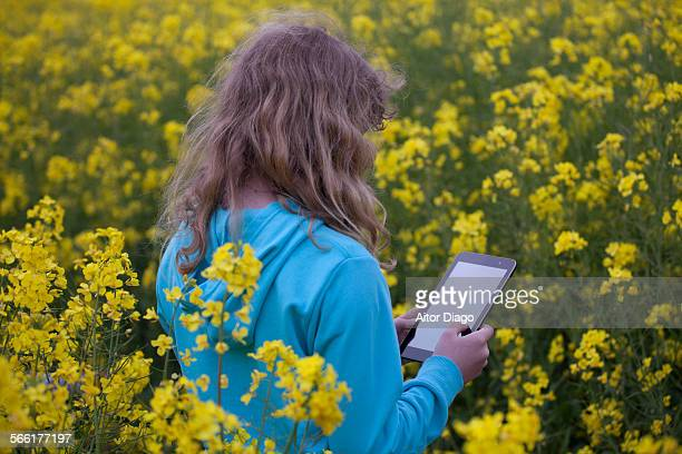 Back view of girl using at tablet in rape field