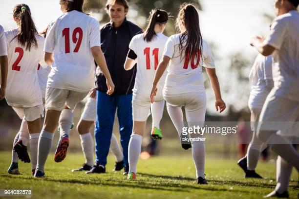 vue arrière du groupe de joueurs de soccer féminin échauffement sur un terrain de jeu. - football féminin photos et images de collection