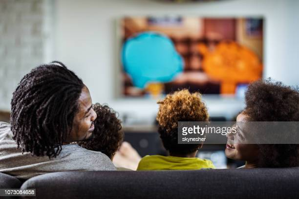 Back view of happy black parents talking while watching TV with their kids at home.