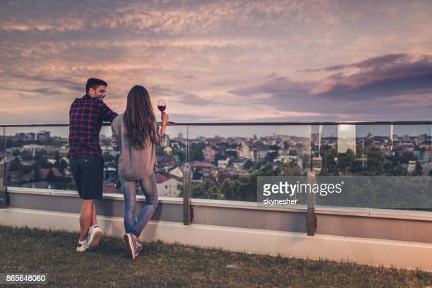 back view of happy couple communicating on a penthouse balcony. - women of penthouse stock photos and pictures