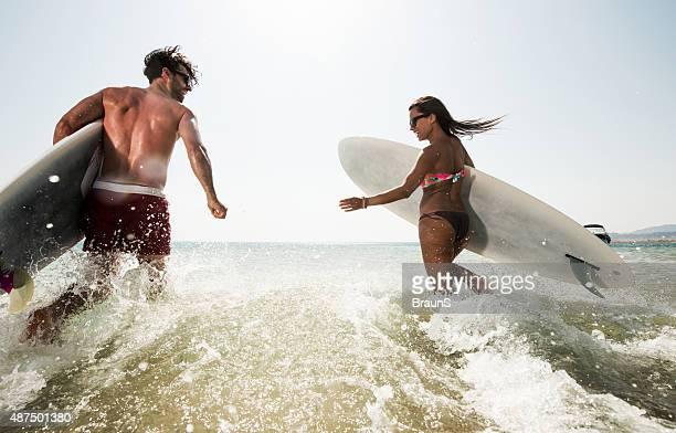 バックのカップルに付き surfboards 海を実行します。