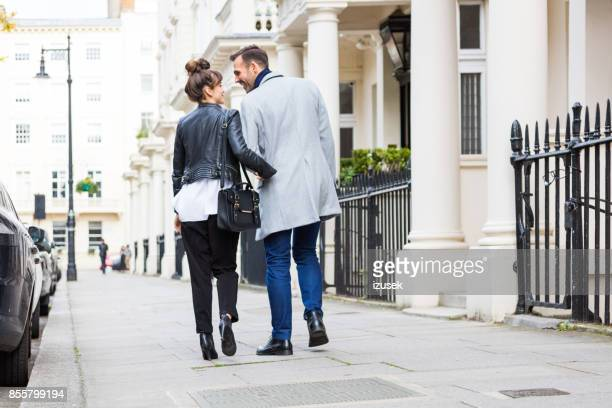 back view of happy elegant couple walking in the city street - bloomsbury london stock photos and pictures
