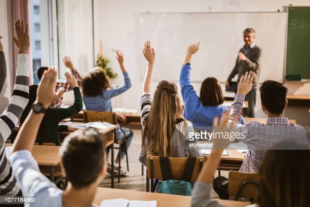 back view of  high school students raising hands on a class. - classroom stock pictures, royalty-free photos & images