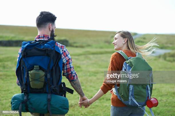 Back view of hipster hiking couple holding hands.