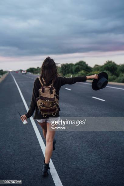 back view of hitchhiking young woman with backpack and beverage standing at side line - hitchhiking stock pictures, royalty-free photos & images