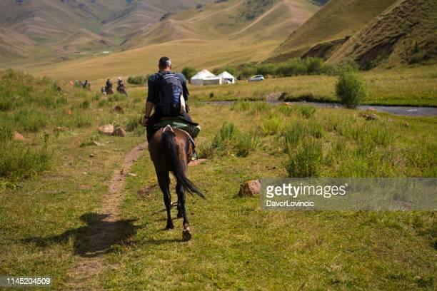 kochkor の近くの山での乗馬の男のバックビュー, キルギス - キルギス ストックフォトと画像