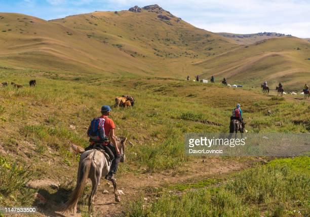back view van ruiters in grasland op weg naar rustplaats op weg naar lake song kol, kirgizië - kirgizië stockfoto's en -beelden