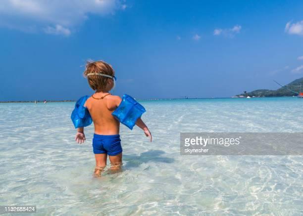 ビーチで水の中に立っている間に水の翼を身に着けている子供のバックビュー。 - 浅い ストックフォトと画像