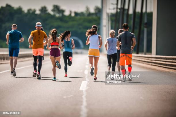 Back view of large group of athletic people running a marathon on the road.