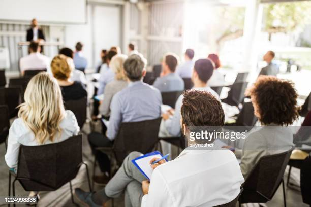 back view of large group of entrepreneurs on a seminar. - conference centre stock pictures, royalty-free photos & images