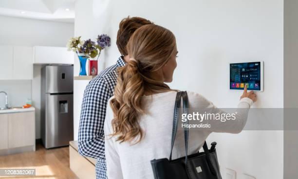 retro vista della coppia latinoamericana che attiva il proprio sistema di smart home - internet delle cose foto e immagini stock