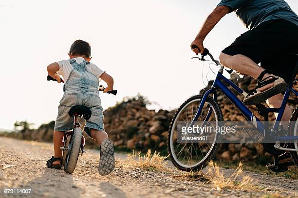 Back view of little boy and his great-grandfather on bicycle tour