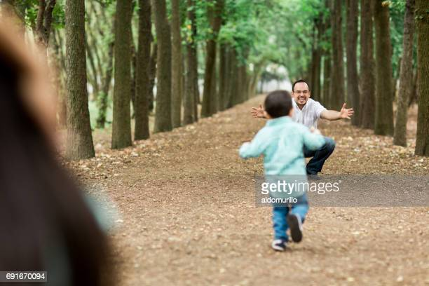 Back view of little boy running to his father