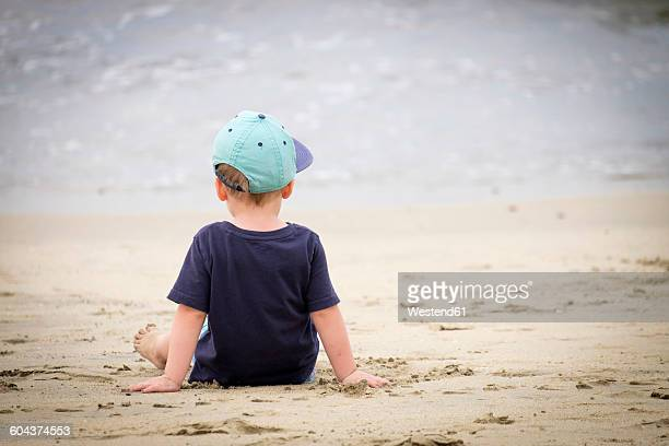 Back view of little boy sitting on the beach at seafront
