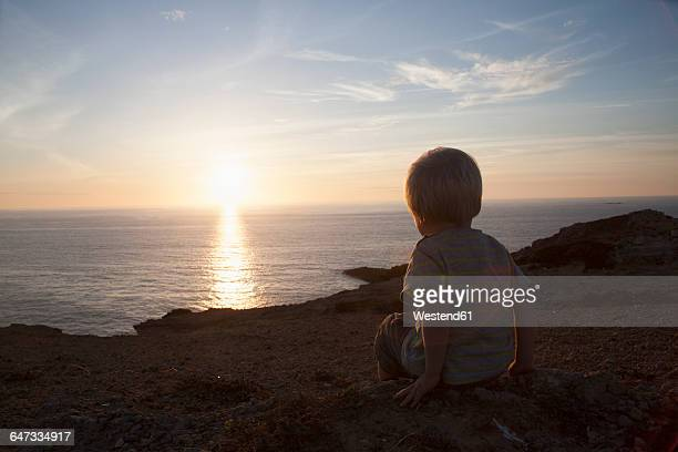 Back view of little boy watching sunset