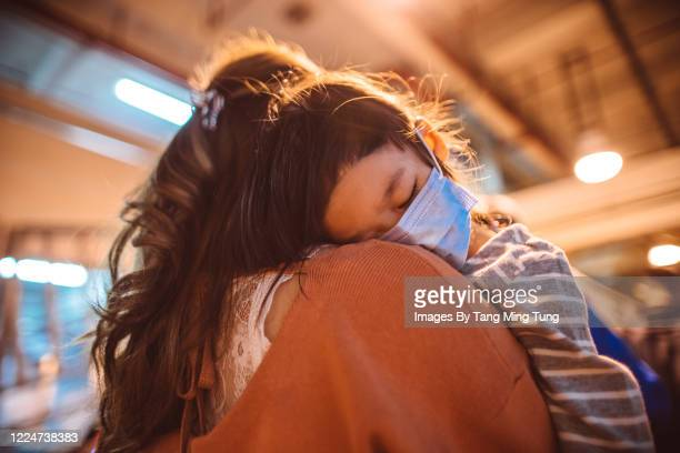 back view of little girl in medical face mask falling asleep on mom's shoulder - asia stock pictures, royalty-free photos & images