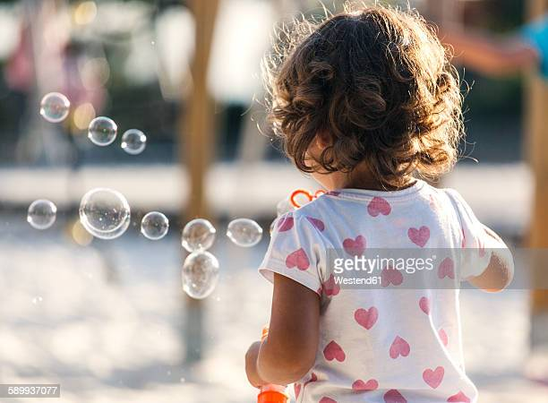Back view of little girl making soap bubbles at playground