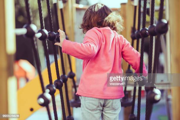 Back view of little girl on climbing frame at playground