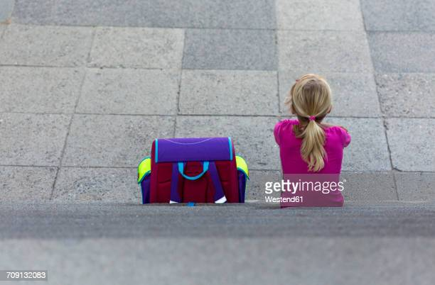 Back view of little girl with school bag sitting on stairs
