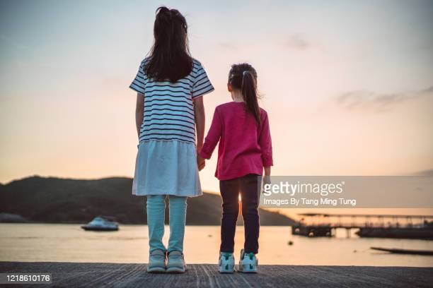 back view of little sisters admiring the sunset together in pier - side by side stock pictures, royalty-free photos & images