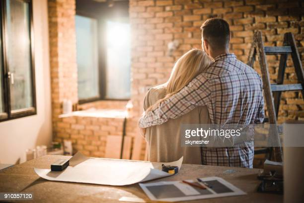 Back view of loving couple standing embraced in their developing apartment.