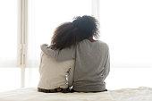 Back view of loving mom hug teen daughter