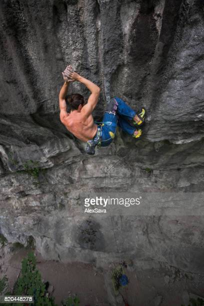 Back view of male rock climber hanging on safety rope