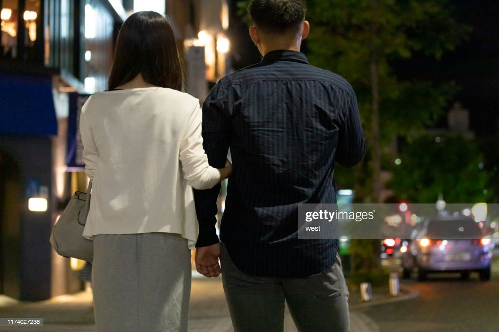 Back view of man and woman walking holding hands in downtown at night : Stock Photo