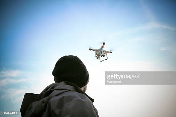 back view of man flying drone - drone photos et images de collection