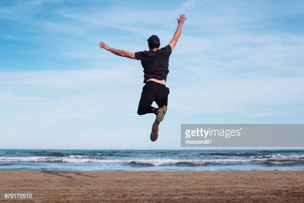 Back view of man jumping in the air on the beach