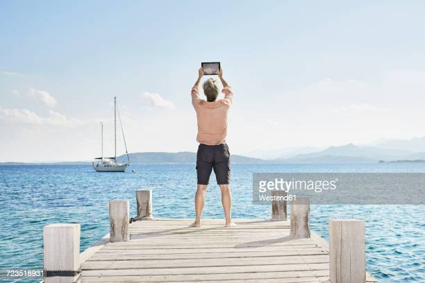 Back view of man standing on jetty taking selfie with tablet