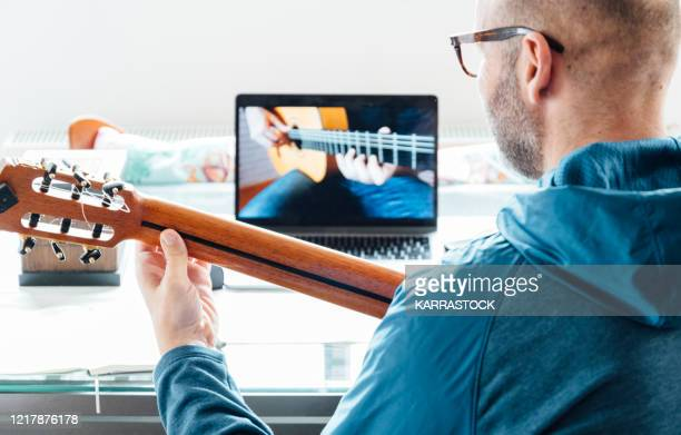 back view of man taking guitar lessons at home. - musical instrument stock pictures, royalty-free photos & images