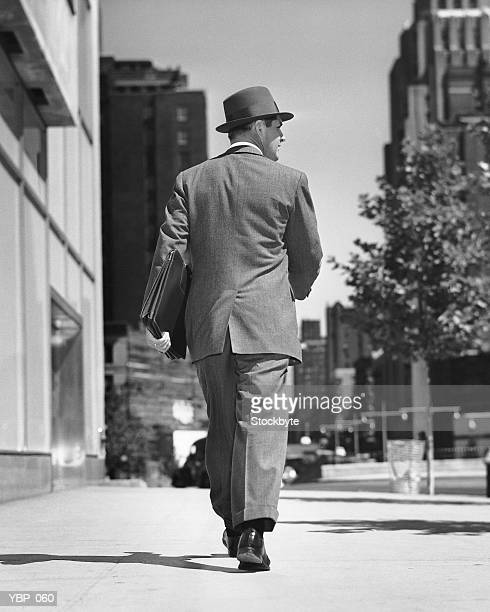 back view of man walking on street - fedora stock pictures, royalty-free photos & images