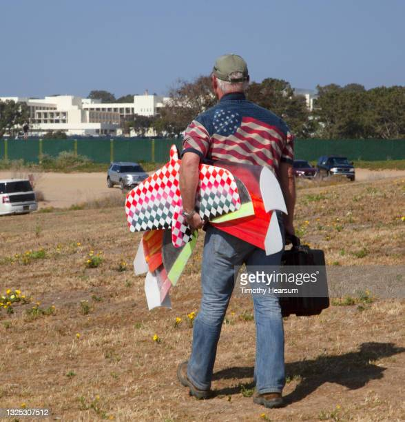 back view of man wearing american flag shirt carrying an array of colorful radio-controlled gliders to a parking lot - timothy hearsum photos et images de collection