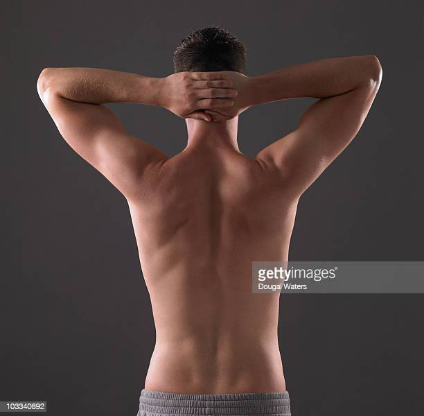 Back view of man with arms stretched behind head.