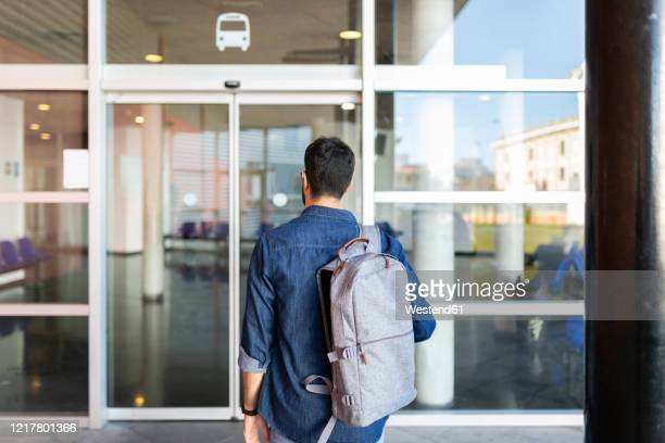 back view of man with backpack in front of entrance of bus station - sliding door stock pictures, royalty-free photos & images