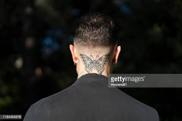 Back view of man with tattooed butterfly on his neck