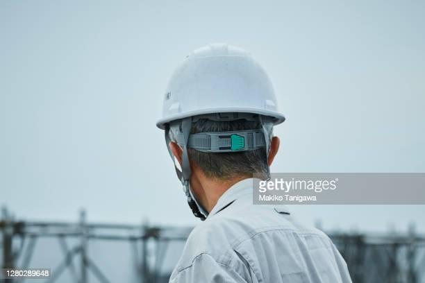 back view of mature construction worker - オーバーオール ストックフォトと画像
