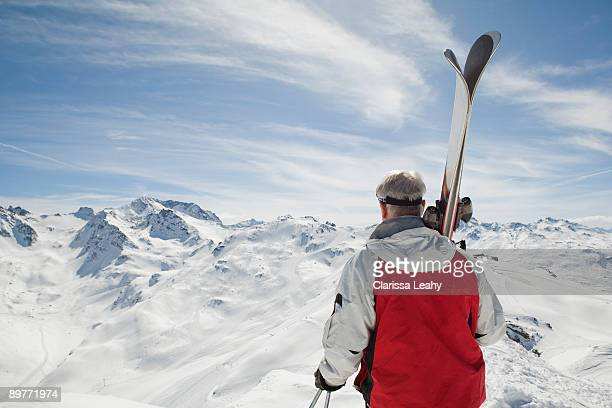 Back view of mature man holding ski's