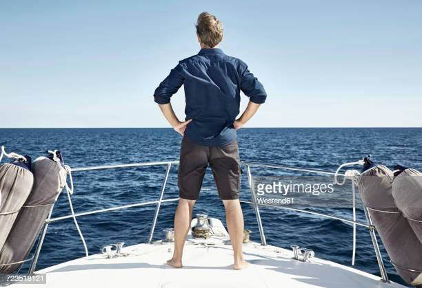 back view of mature man standing on his motor yacht with hands on hips - handen op de heupen stockfoto's en -beelden