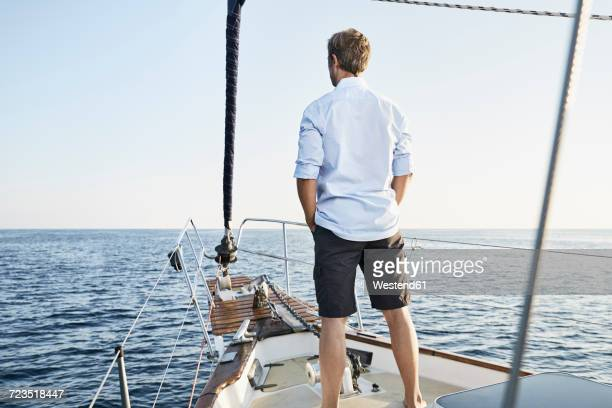back view of mature man standing on his sailing boat looking at distance - rear view stock pictures, royalty-free photos & images