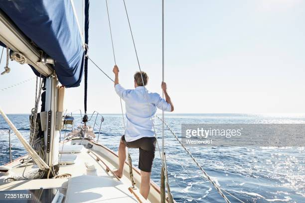 back view of mature man standing on his sailing boat looking at distance - tuig mast stockfoto's en -beelden