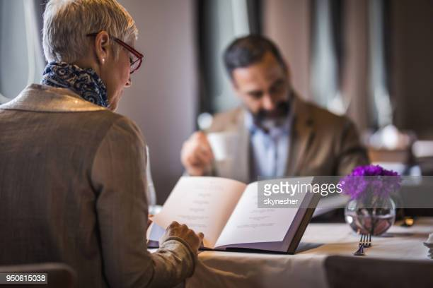back view of mature woman reading menu during lunch time in a restaurant. - menu stock pictures, royalty-free photos & images